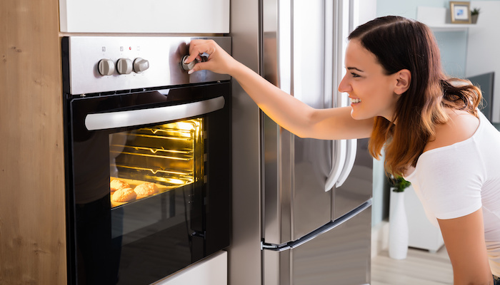 woman looking at oven appliance